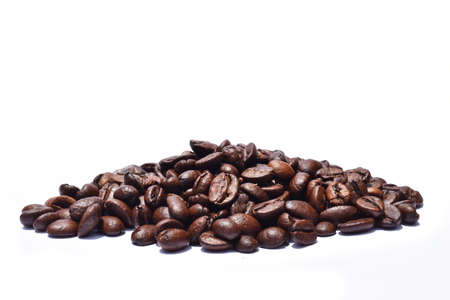 Pile of Dark brown roasted coffee beans isolated on white background, Raw processed food for drinks refreshment