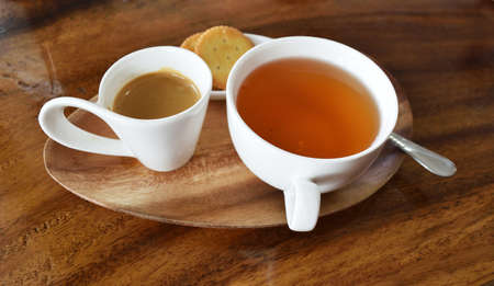 Espresso Coffee with hot tea in white cup and flatbread crackers on wooden table