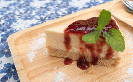 Cheesecake pie slice topped with strawberry syrup and Mint leaves on a wooden plate, Sweet food with  table