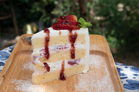 Strawberry syrup and cream sponge cake in a wooden tray on table Banque d'images