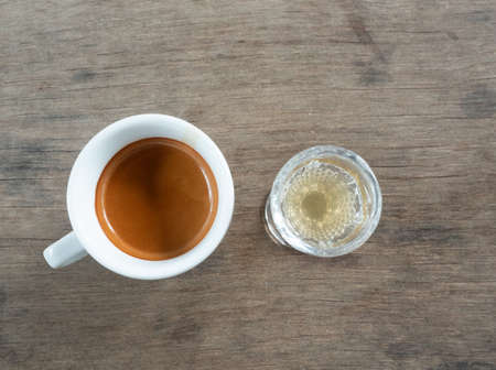 Espresso coffee in a white cup with a glass of honey, Hot drink with gray wooden table in background