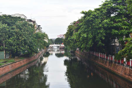 Canal with brown brick walls and green plants reflecting on the water surface, View from the bridge in Bangkok, Thailand