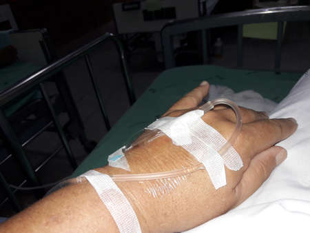 Patients ้and of the men were connected to the saline solution  in hospital bed, Depressing conditions in a nursing facility, IV drip vitamin infusion therapy