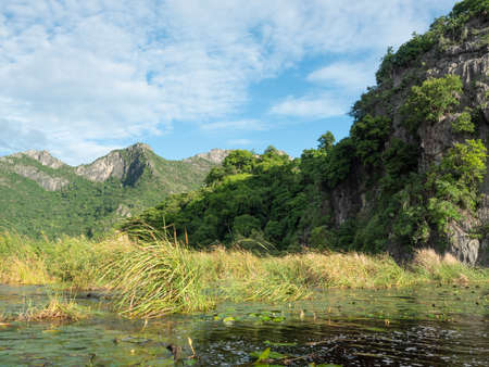 Rock cliff and green forest in lake with blue sky and white could in background, Reflection of Limestone mountain on water of the vast wetland at Khao Sam Roi Yot National Park , Thailand