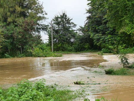 Turbid water from the creek in the rainy season is flooding and is flowing across the road in Thailand