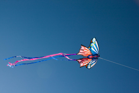 kite flying with butterfly shape with the wind in the blue sky