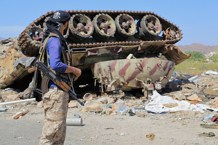 Yemeni soldier stands in front of one of the Houthi militia tanks after being destroyed by coalition aircraft west of the city of Taiz.