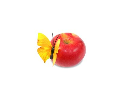 Isolated red apple with artificial yellow butterfly Stock Photo