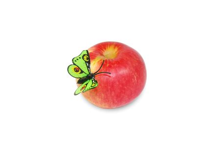 Isolated red apple with artificial green butterfly