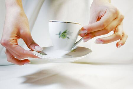 Two hands holding a cup and a saucer
