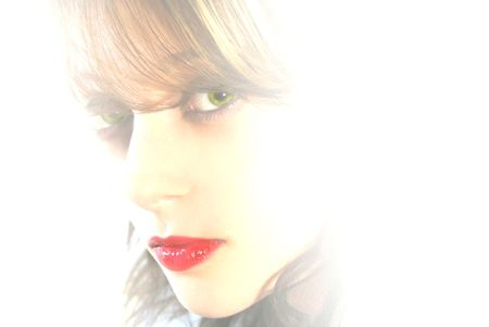 A girl with red lips is surrounded by white light