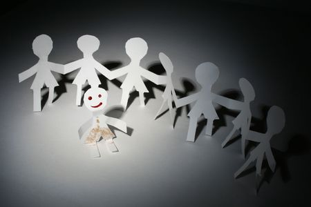 Seven white paper people in chain and one with smile Stock Photo
