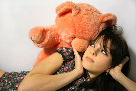 Cute and pretty girl looking at pooh bear toy photo