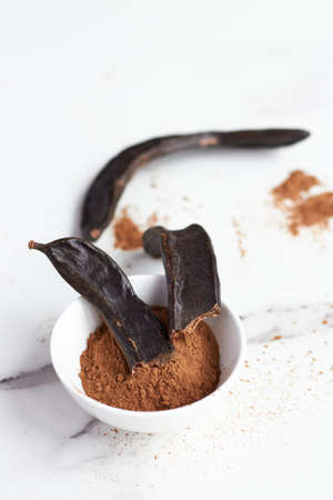 white bowl with carob powder and been in a white surface