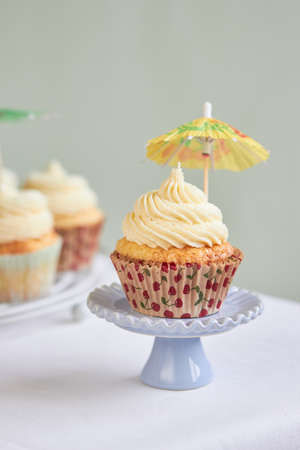 iced cupcake on a tiny cake stand with a papel umbrela