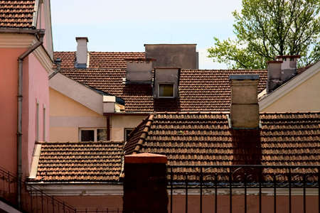 Tile roofs of the old houses with chimneies