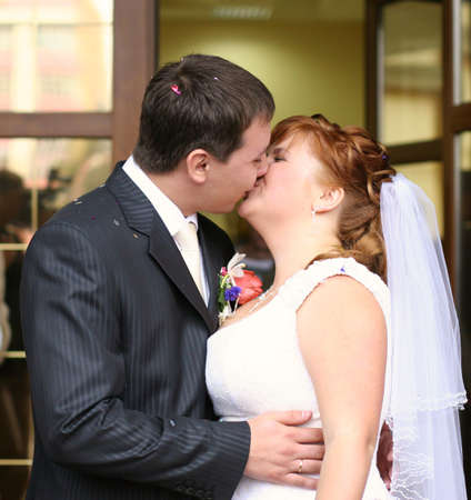 romantic wedding couple (groom and bride) kissing in the street