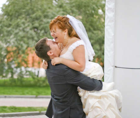 groom embracing laughing plump bride in the park