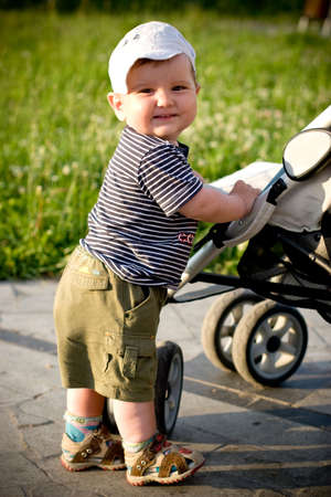 smiling baby standing near the stroller Stock Photo