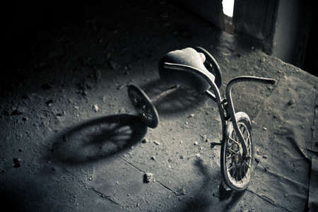 Old dusty tricycle standing on the wooden floor Stock Photo