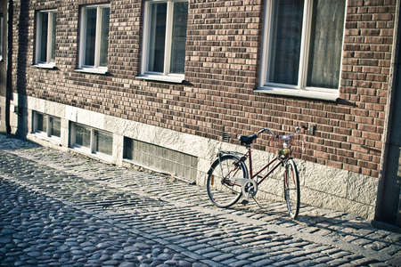 Bicycle standing near the brick wall on the sidewalk