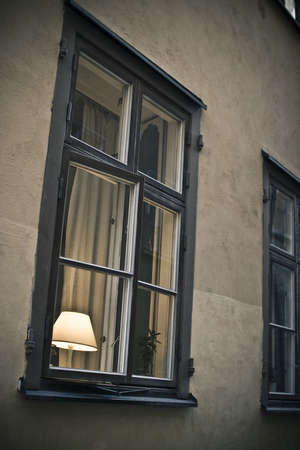 Half-opened window with switched on lamp on the window-sill