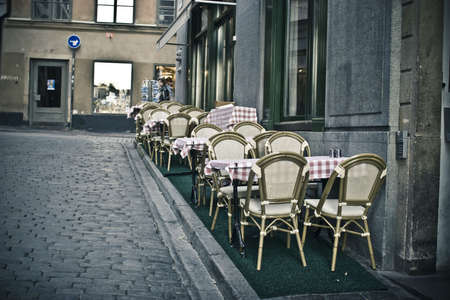 Empty chairs and tables of summer cafe standing on the sidewalk