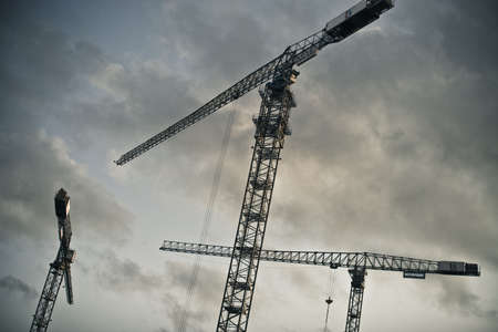Lifting cranes against clouds