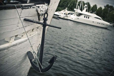Hanging anchor on the wooden yacht