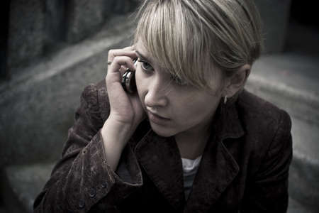 Girl with blonde fringe sitting on the steps and looking sideways while talking by phone