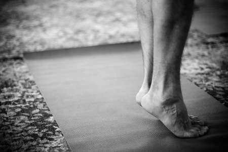 Feet standing on yoga mat photo