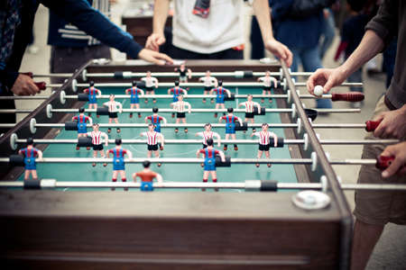 football object: Outdoor green table football board with many colorful figures and a few players around