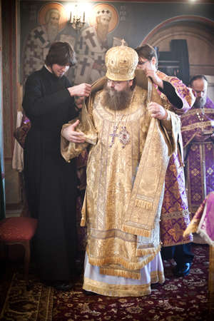 iconostasis: Two monks help the Bishop to robe. Orthodox liturgy with bishop Mercury in High Monastery of St Peter in Moscow on March 14, 2010 in Moscow