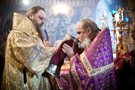 high priest: The priest drinks wine during communion. Orthodox liturgy with bishop Mercury in High Monastery of St Peter in Moscow on March 14, 2010 in Moscow