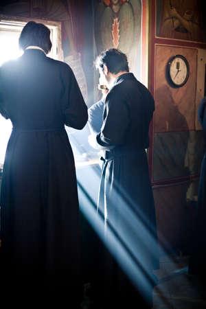 sacerdote: Dos monjes comer después de la liturgia junto a la ventana llena de luz. Liturgia ortodoxa con el obispo de mercurio en el Monasterio Alto de San Pedro en Moscú el 14 de marzo de 2010 en Moscú