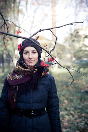 Young girl dressed in dark coat, knitted cap and shawl with flower pattern is standing under the pale sky, trees and grass on the background Stock Photo - 10775365