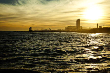 Bright yellow sundown seascape with silhouettes of Barcelona's high-rise buildings and harbor cranes on the background