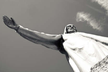 outspread: Monochrome close-up of Jesus Christ statue with outspread right hand; sky and few clouds on the background Stock Photo