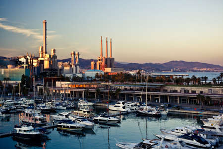 Barcelonas marina with many yachts and boats; modern cityscape with industrial buildings, pipes and far mountains on the background