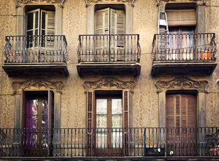 A few old-fashioned balconies with steel fence and with different things on, placed above each other on the pastel wall with ornamental pattern Stock Photo