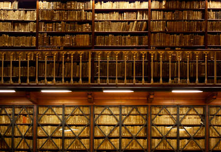 Many old books are standing on wooden shelves in two-tier library , with handrail on foreground