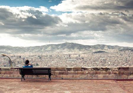 barcelone: L'homme est assis sur le banc et regarder le paysage urbain et les montagnes � l'arri�re-plan