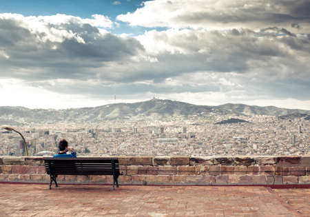 city square: Man is sitting on the bench and looking at the cityscape and mountains at the background