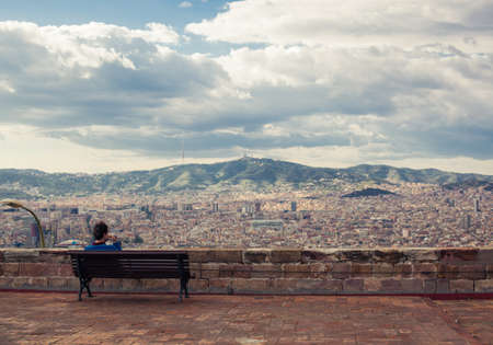 Man is sitting on the bench and looking at the cityscape and mountains at the background