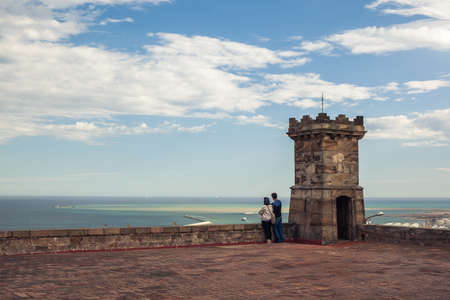 stratus: Couple is standing near the one of Castell de Montjuic's small towers with opened doorway and looking at the horizon, with sea and sky at the background