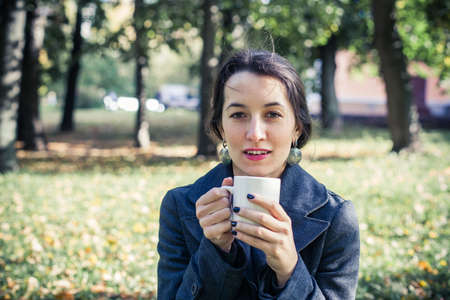 Girl in an autumn part with a white cup of hot drink Stock Photo - 17242112