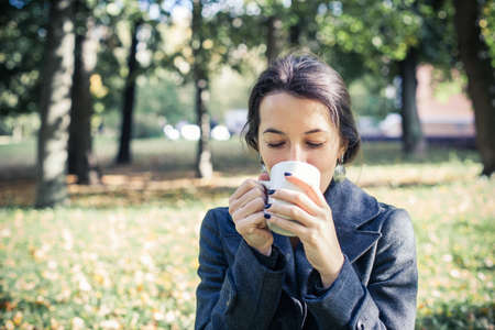 Girl in an autumn part with a white cup of hot drink Stock Photo - 17242111