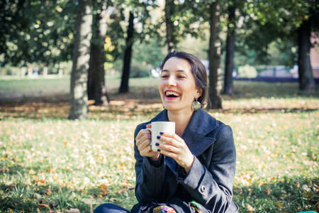 Girl in an autumn part with a white cup of hot drink