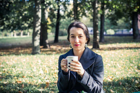 Girl in an autumn part with a white cup of hot drink Stock Photo - 17242110