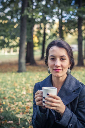 Girl in an autumn part with a white cup of hot drink Stock Photo - 17242144